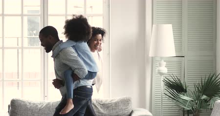 den matek : Active afro american family of four parents carry piggyback two little cute kids play funny lifestyle game together in living room, happy african mum and dad having fun enjoy leisure activity at home