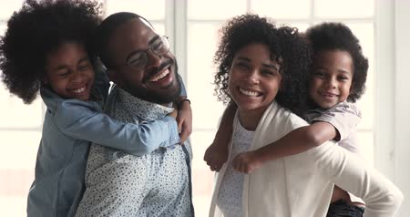 Happy african american family young adult parents father mother piggyback small cute mixed race children son and daughter laugh playing together in living room look at camera stand at home, portrait