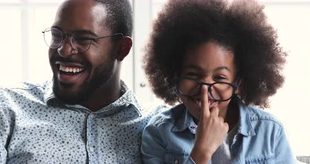 Funny cute small african american kid daughter copy cheerful adult dad wear glasses and laughing looking at camera, adorable happy ethnic family father with child girl having fun playing at home