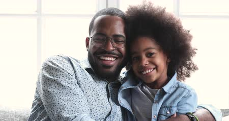 Smiling affectionate african american family adult dad and small cute child daughter look at camera laugh cuddle, loving ethnic father hug preschool kid girl bonding embracing give high five at home Vídeos