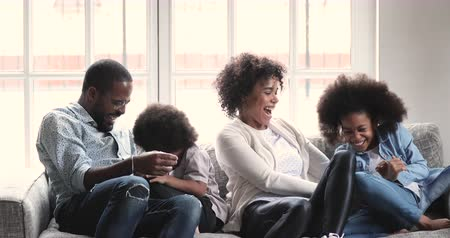 Cheerful affectionate afro american family having fun relaxing on sofa, happy african adult parents tickling laughing cuddling at home playing lifestyle game bonding enjoying funny moments at home Vídeos