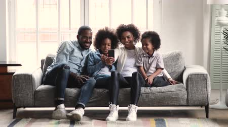 Young african american parents and small children preschoolers watching recording social media video story making video call or using phone tech camera ar application sit on couch in living room