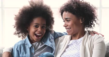 Loving happy african american family young adult mum and cute preschooler mixed race child kid daughter laughing cuddle having fun sit on sofa look at camera enjoy sweet moment play at home together