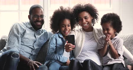 usuário : Happy african family parents and small children laugh using smart phone gadget relax together on sofa, mixed race mom dad preschool kids hold look at smartphone screen use funny ar mobile app at home