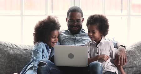 Smiling young adult african american dad and two small kids enjoying using laptop together watching funny videos laughing playing online surfing web on modern computer device relaxing on sofa at home