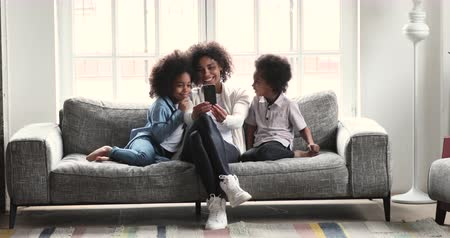Happy young african mum using social media app on smartphone recording video blog watching stories listening music having fun with two cute small kids looking at mobile phone relaxing on sofa at home Vídeos