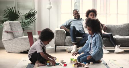 Happy afro american family spend weekend in cozy modern living room, two cute small african kids son daughter playing on floor and young parents couple relax on sofa enjoy leisure activities at home