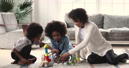 Happy young adult african parent mom babysitter playing wooden blocks and dinosaurs toys with cute kids small son and daughter sit on warm floor carpet enjoy weekend activity in living room at home Vídeos