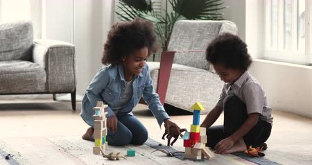 zabawka : Two happy cute preschool african children siblings boy and girl play toys game sit on floor carpet at home, 2 small mixed race kids having fun with wooden blocks dinosaurs together in living room Wideo
