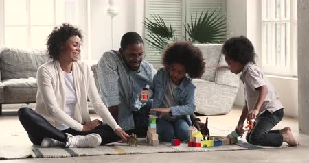 zabawka : Happy family young adult african parents mum dad and two small children kids preschoolers play toys dinosaurs building castle of wooden blocks sit on floor enjoy activity game in living room together