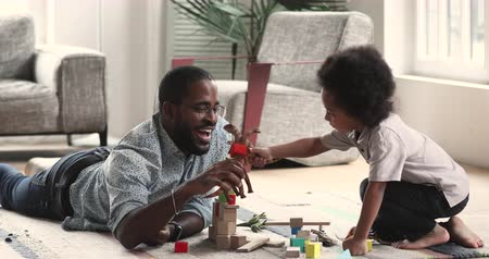 zabawka : Happy african parent father and kid son playing toys pretend dinosaurs battle at home, afro american dad having fun enjoy game activity with little child boy together on floor carpet in living room