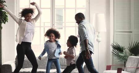 Happy carefree african american ethnic couple dancing with cute active preschool small children in living room interior together, family mortgage and parents with kids weekend fun at home concept