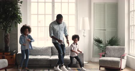 Funny afro american little children preschoolers dance copy young adult father in living room interior, happy african family dad babysitter and two active energetic kids having fun at home together