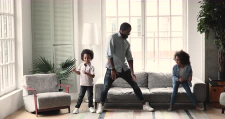 babysitter : Happy active african american dad teaching dancing having fun with two cute small kids son and daughter imitate father moves playing together enjoying funny weekend activity in modern living room