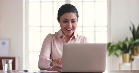 pozitivity : Excited indian business woman winner celebrate online win success look at laptop, happy female worker read good internet email news get promotion achieve new opportunity concept at work in office