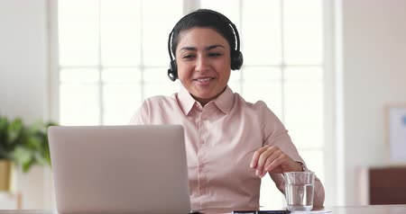 konferencja : Happy indian business woman winner wear wireless headset conference calling on laptop doing video chat celebrating victory good news about success getting hired during distance job interview concept