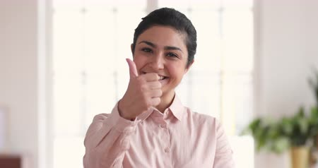 kciuk : Happy confident young indian ethnic professional business woman winner showing thumbs up like hand gesture in office recommend good job best quality corporate services for career success concept