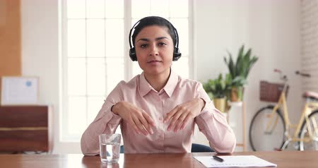 temsilci : Confident indian ethnic business woman wear wireless headset looking talking to webcam, female professional company representative speak to camera conference calling by video chat concept in office