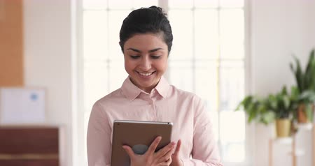 босс : Happy indian female professional manager business woman using digital tablet computer apps standing in modern office, smiling ethnic businesswoman working on business technology corporate device