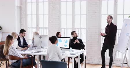 speaker : Young businessman professional coach business trainer designer give presentation on flip chart teaching team staff at conference lecture office meeting conducting marketing workshop training concept Stock Footage
