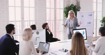 konferencja : Professional mature middle aged business woman coach manager designer boss conduct corporate workshop give flip chart presentation concept discuss project with team at office group meeting training