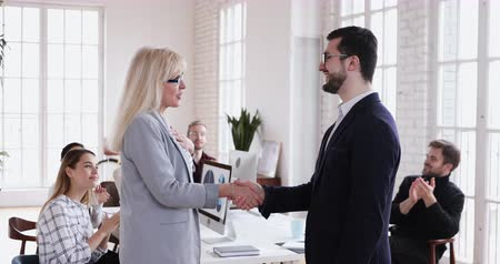 juntar : Happy boss handshake recognize promote mature female employee appreciate for good work results, proud middle aged businesswoman get corporate gratitude, personal respect applause in office concept