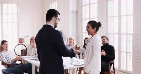 босс : Proud male executive manager congratulate handshake promote praise female indian worker intern get rewarded for professional skills shake hand of boss with team applause, employee recognition concept Стоковые видеозаписи