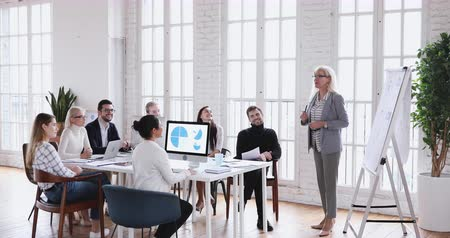 speaker : Confident middle aged female leader mature older executive manager speaking at group training teaching happy company workers at professional education sales workshop meeting in modern office room