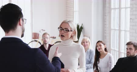 ösztönző : Happy confident young businesswoman get promoted handshaking male boss appreciating best female worker for good work result while team clap hands give positive feedback and staff incentive concept Stock mozgókép