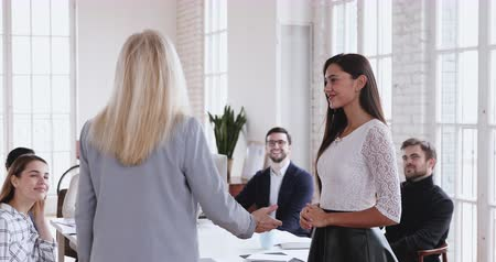 босс : Happy young best female worker trainee intern being appreciated promoted handshake older executive, mature boss praising rewarding thanking millennial employee express respect and recognition concept Стоковые видеозаписи