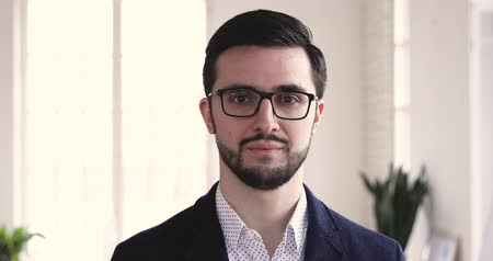 konsultant : Smiling confident young professional business man professional manager executive wear suit glasses look at camera, happy handsome male ceo entrepreneur leader stand in office, close up face portrait