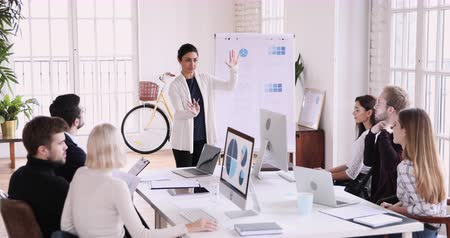 speaker : Professional confident indian female coach manager speaking during marketing workshop training designers group give flip chart presentation explaining analyzing research data at team office meeting