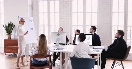 speaker : Confident young businesswoman speaker coach presenting educational course teaching diverse business people group at corporate office training workshop seminar give flip chart presentation concept