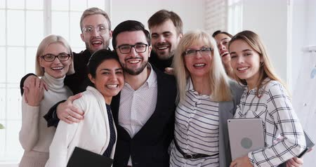 lider : Happy successful multi ethnic dream team looking at camera bonding, cheerful friendly diverse ethnicity staff employees group embracing laughing stand in corporate office posing for business portrait Stok Video