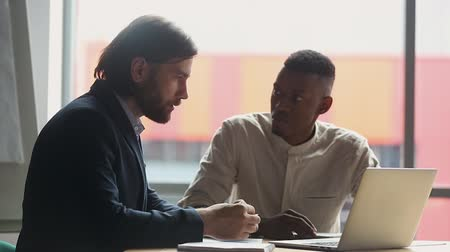Confident caucasian manager explaining corporate software to young african american employee. Skilled supervisor discussing working moments with motivated millennial mixed race teammate at office.