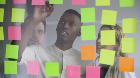 briefing : Focused young african american team leader writing notes on colorful paper stickers on glass wall at modern office. Successful mixed race teammates managing tasks together near kanban board.