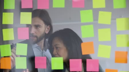 босс : Confident male worker managing project tasks with middle aged korean supervisor at kanban glass board. Motivated younger and older colleagues writing notes on colorful sticky papers in modern office.