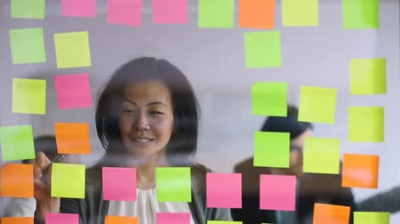 タスク : Smiling middle aged mature businesswoman working near window wall with colorful stickers, replacing tasks. Happy older korean female worker managing project processes, using kanban glass board. 動画素材