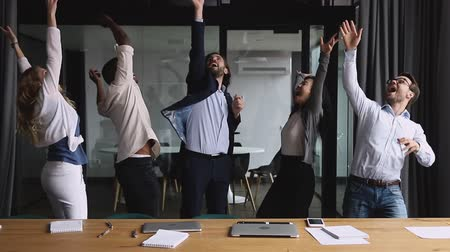 lider : Happy multiracial colleagues dancing in office, throwing papers in air, celebrating corporate success. Excited mixed race different generations motivated teammates enjoying victory dance at workplace.