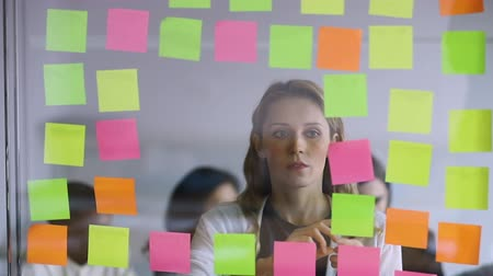 procedimento : Focused young female project manager replacing colorful stickers, planning working process on glass wall. Motivated businesswoman managing workflow, using window kanban board in modern office.