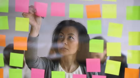 задумчивый : Concentrated mature korean female manager writing notes on colorful paper stickers, placed on kanban glass board. Focused successful middle aged asian businesswoman managing project processes on wall. Стоковые видеозаписи