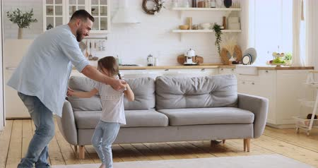 Smiling young handsome dad holding hands of cute small daughter, dancing barefoot on carpet in modern kitchen studio room. Happy carefree active family of two laughing, having fun together at home.