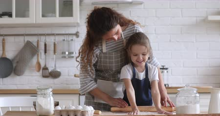 vazba : Smiling pleasant young mother and little preschool daughter in aprons preparing dough for bakery together in modern kitchen. Attractive woman teaching small kid girl baking homemade pizza cookies. Dostupné videozáznamy