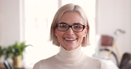 lider : Smiling confident young adult blonde businesswoman manager professional wear glasses looking at camera in corporate office, happy smart millennial female model worker manager close up face portrait