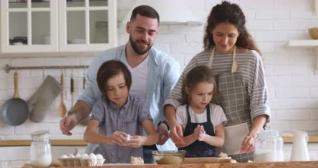 Happy full family kneading dough, having fun together at home. Smiling married couple playing with joyful little kids siblings while making homemade bakery, enjoying spending free time in kitchen.
