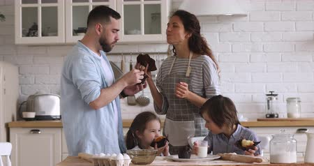 milující : Happy young couple enjoying fresh homemade muffins with smiling kids siblings in modern kitchen. Excited full family satisfied with cooking results, eating bakery products together at home.