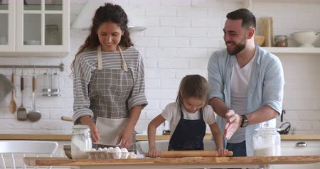 Overjoyed married couple playing with flour while little preschool daughter learning using rolling pin in modern kitchen. Happy full family having fun, preparing homemade bakery together at home.