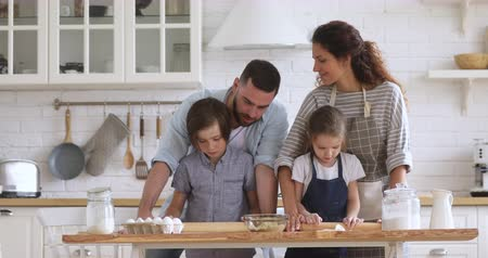 Smiling couple teaching children siblings flattening dough with rolling pins together in modern kitchen. Happy full family preparing homemade food, involved in baking activity on weekend at home.