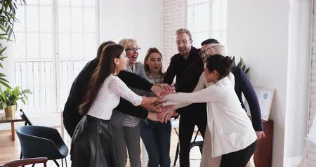 обещание : Multiethnic employees stack hands engaged in corporate loyalty and cooperation, diverse ethnicity professional team people express trust unite in shared goal responsible for teamwork result concept