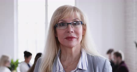 тренер : Smiling mature adult business woman wear glasses looking at camera, confident middle aged female corporate leader director manager teacher executive mentor posing in office, closeup business portrait